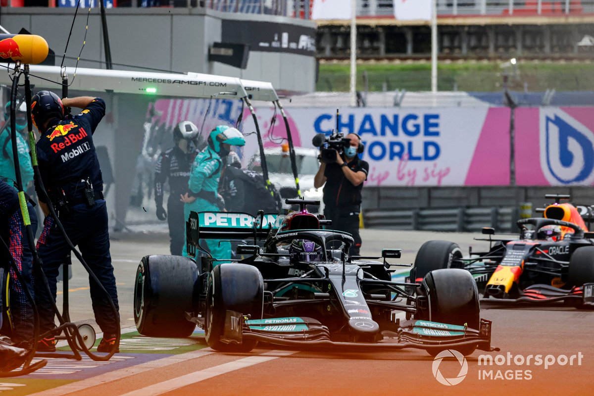 Lewis Hamilton, Mercedes W12, leaves his pit box as Max Verstappen, Red Bull Racing RB16B, comes in for a stop