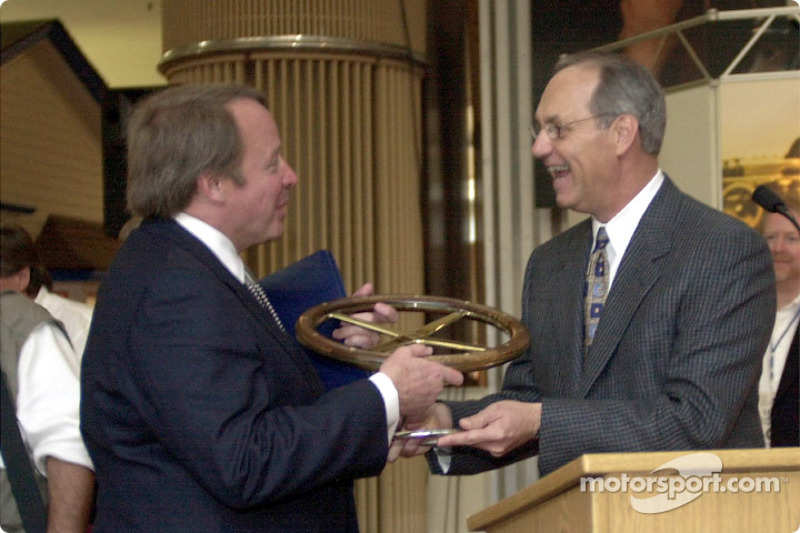 Dan Davis, on right, Director of Ford Racing Technologies, presents a commemorative steering wheel to Edsel B. Ford II, during a ceremony to unveil a restored Ford 1901 Sweepstakes