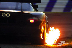The #3 Jaguar belches flame as it rounds the International Horseshoe