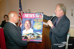 NHRA announcer Dave McClelland present a SEMA cover to George deBidart for bring the Grand Prix to DC