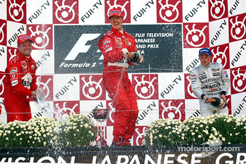 The podium: champagne for Michael Schumacher, Rubens Barrichello and Kimi Raikkonen
