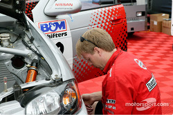 A TeamRTR crew member changes springs on the #1 car