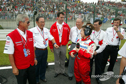 Akihiko Saito and Fujio Cho with other team members on the starting grid
