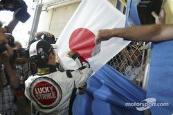 Takuma Sato signs a Japanese flag