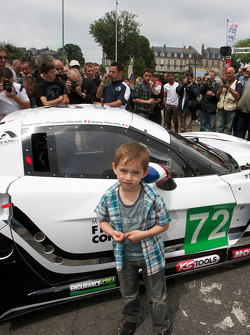 A young fan poses with the #72 Luc Alphand Aventures Corvette C6.R