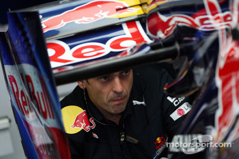 A mechanic looks at the rear of the Red Bull
