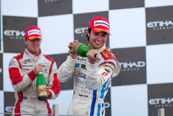 Sergio Perez celebrates his victory on the podium with Sam Bird