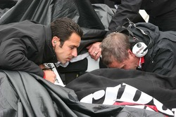 Helio Castroneves helps work on the car during the rain showers