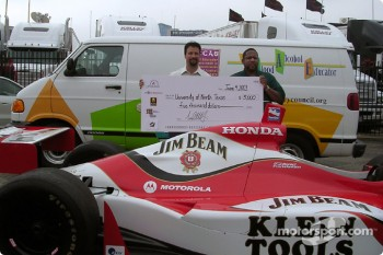 Michael Andretti presents a $5000 check to University of North Texas' health center executive director Reginald Bond