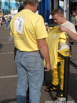 Fans greet A.J. Allmendinger with a commemorative ChampCar start T-shirt