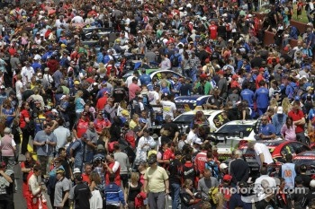 A huge crowd surrounds the cars