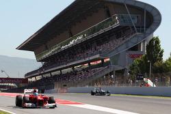 Fernando Alonso, Ferrari leaves the pits as Michael Schumacher, Mercedes AMG F1 passes