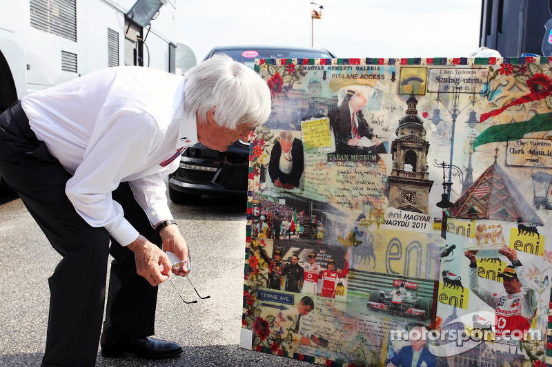 Bernie Ecclestone, CEO Formula One Group, takes a closer look at a Hungarian Grand Prix montage by artist Mark Dickens