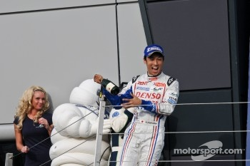 Kazuki Nakajima threatens Bibendum man and a grid girl with champagne