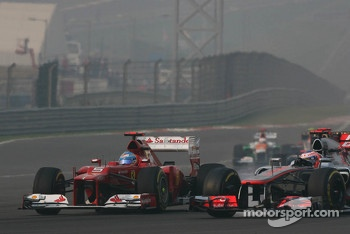 Fernando Alonso, Ferrari and Jenson Button, McLaren battle for position at the start of the race