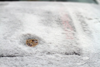 Porsche logo covered in snow