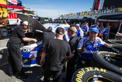 Michael Waltrip Racing Toyota crew members repair the wrecked car of Mark Martin