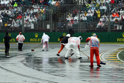Marshals clear the track of rain water