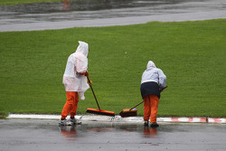 Marshals clear rain water from the circuit