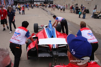 A.J. Foyt Enterprises crew members push the car out
