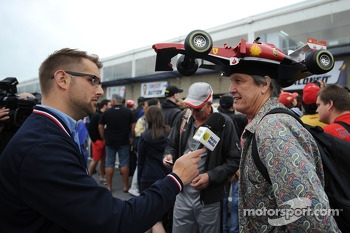 A fan with a Ferrari on his head