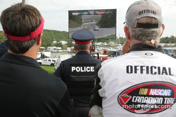 Police and NASCAR official watching the end of the race on the big screen in pit row