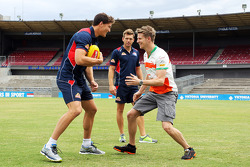 Nico Hulkenberg, Sahara Force India F1 practices his Aussie Rules skills on Will Minson, Western Bulldogs Australian Rules Footballer, and Shaun Higgins, Western Bulldogs Australian Rules Footballer, at Whitten Oval