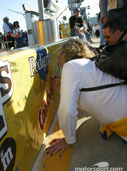 Fans write good luck messages to their favorite drivers on the pitwall banners