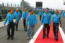 Giancarlo Fisichella returns from a track walk with Pat Symonds and Renault team members