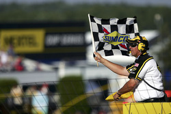 Flagman Rick Monroe waves the checkered and yellow flags
