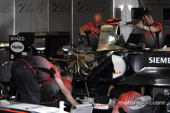 McLaren team members work on the engine