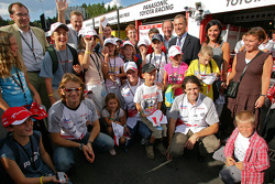 Jarno Trulli, Ralf Schumacher and Ricardo Zonta pose with young fans