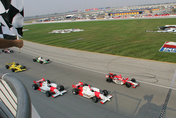 Dan Wheldon takes the checkered flag ahead of Helio Castroneves and Sam Hornish Jr.