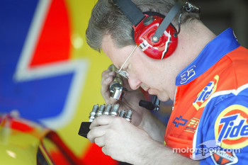A Tide Chevy crew member inspects spark plugs