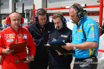 Ferrari, Williams and Renault team members keep an eye on each others notes