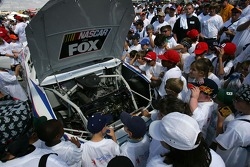 A group of 400 school children look at an engine of a NASCAR stock car prior to the Neighborhood Excellence 400 presented by Bank of America