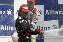 Giorgio Pantano celebrates victory on the podium with Alexandre Premat