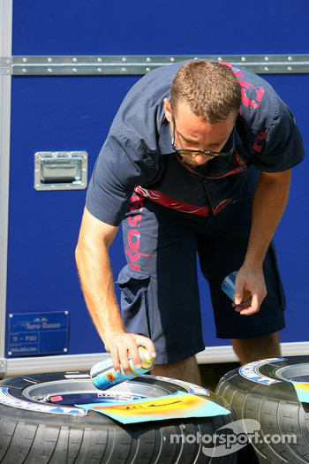 Torro Rosso mechanic marking the tyres
