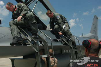 Col. Chris 'Bert' Colbert and Tony Raines climb into the cockpit of an F-16 at Hulman Field in Terre Haute, Indiana