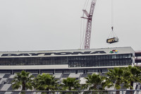 A crane takes away the first piece of the Daytona press box and suite facility
