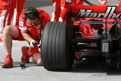 A mechanic works on the wheel of Felipe Massa