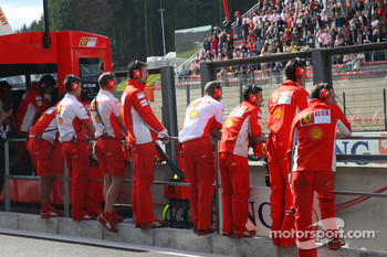 Ferrari mechanics watch the cars making practice starts