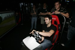 Petit Preview Party at Atlantic Station: Lucas Luhr tries the racing sim at the Fox Sports Grill party, while Dirk Muller looks on