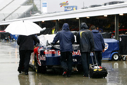 The #83 Red Bull team pushes the car through the rain at Martinsville