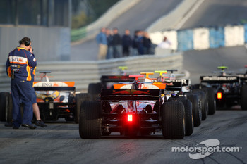 Cars wait for the lights to change at the end of the pitlane