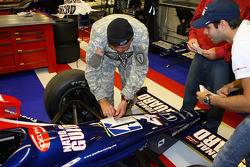 A National Guard General places a decal on the No. 4 Panther Racing car driven by Vitor Meira