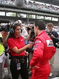 Helio Castroneves conducts a TV interview after his qualifying run