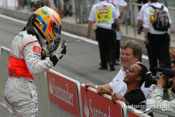 Race winner Lewis Hamilton celebrates with his brother Nick and Norbert Haug