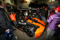 A young fan sits in a KTM X-Bow in the paddock