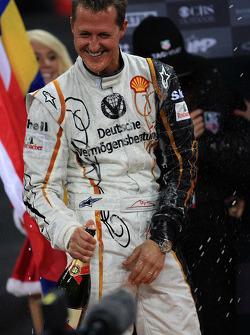 Podium: Michael Schumacher sprays champagne